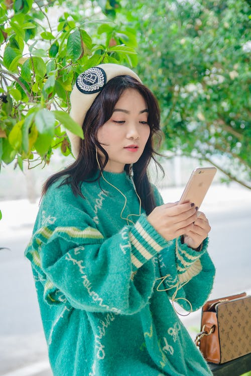 Pretty Woman in Green Sweater Using a Mobile Phone