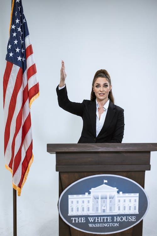 Woman in Black Blazer Beside USA Flag
