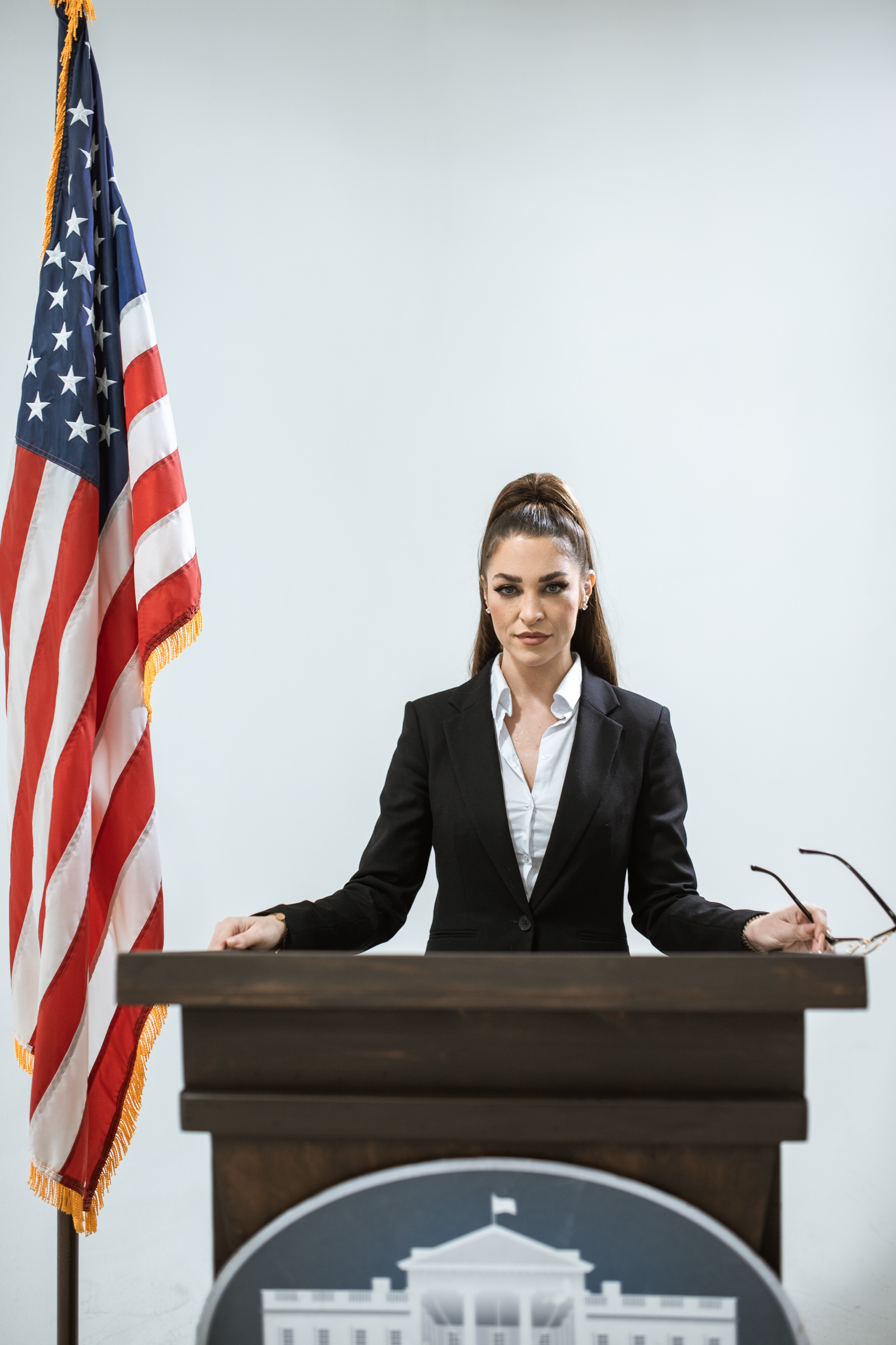 photo of woman standing behind wooden table