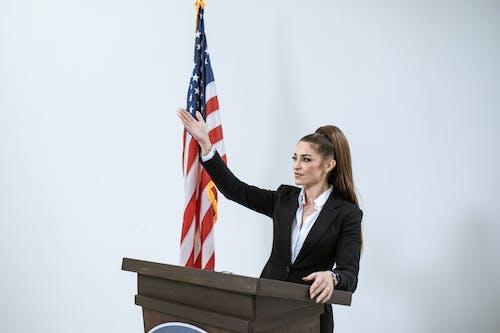 Woman in Black Blazer Standing Behind a Podium