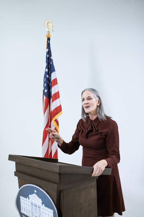 Woman In a Dress Speaking Behind a Podium