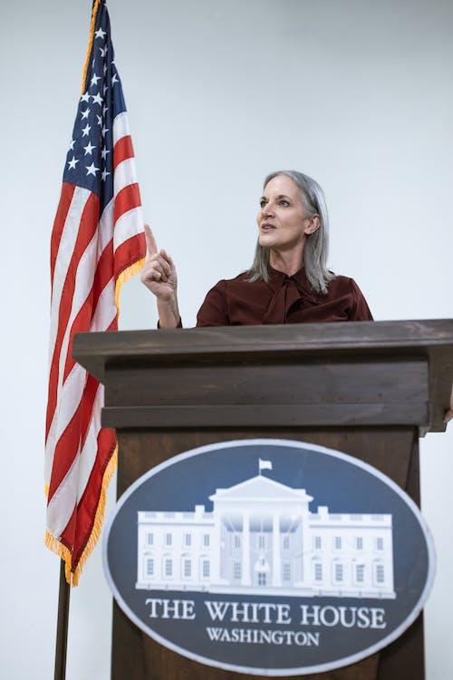 Woman Behind a Brown Podium