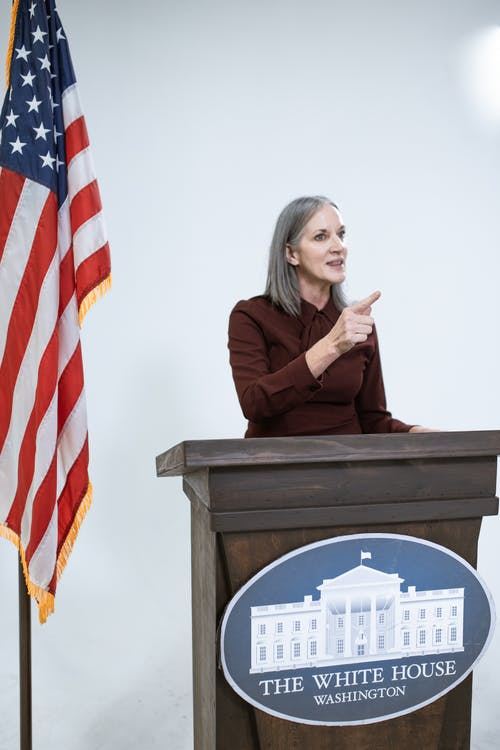 Woman in Maroon Dress Speaking Behind a Podium
