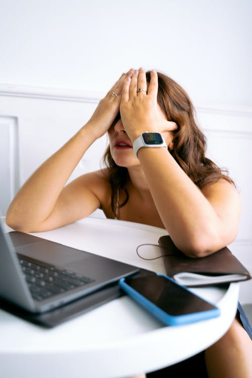 Woman in Black and White Watch Sitting on Chair in Front of Laptop Computer
