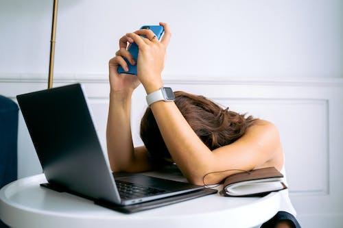 Woman in Black Tank Top Using Black Laptop Computer