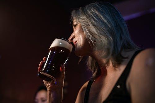 Женщина пьет из прозрачного стакана