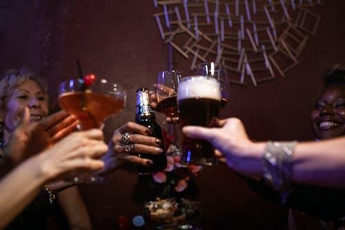 Люди, держащие стаканы с коричневой жидкостью