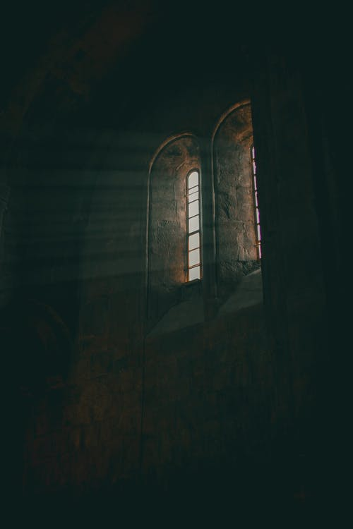 From below of old stone building with arched windows located under ceiling and illuminating dark room
