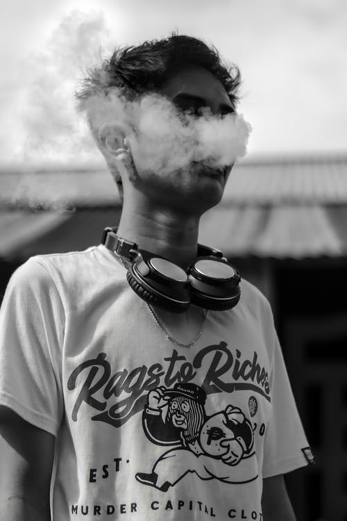 Young male hipster with headphones around neck smoking outdoors