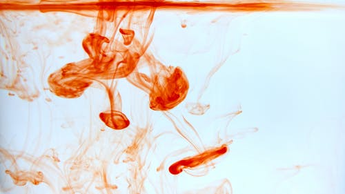 Abstract background of red paint diffusing in clean water and forming jellyfish shapes and splotches