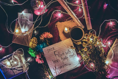 From above of various Christmas decorations and glowing garland placed on table with paper sheets with different written wishes and cup of coffee