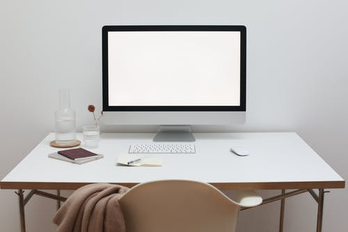 Stylish workspace with computer and simple furniture