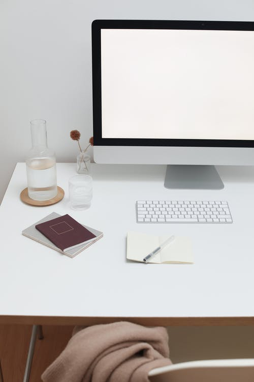 Creative workspace with personal computer and glass bottle with water near paper notebooks