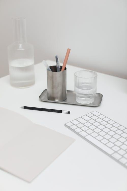 Gelas Plastik Putih Disamping Pulpen Hitam Dan Gelas Plastik Putih Di Atas Meja Putih