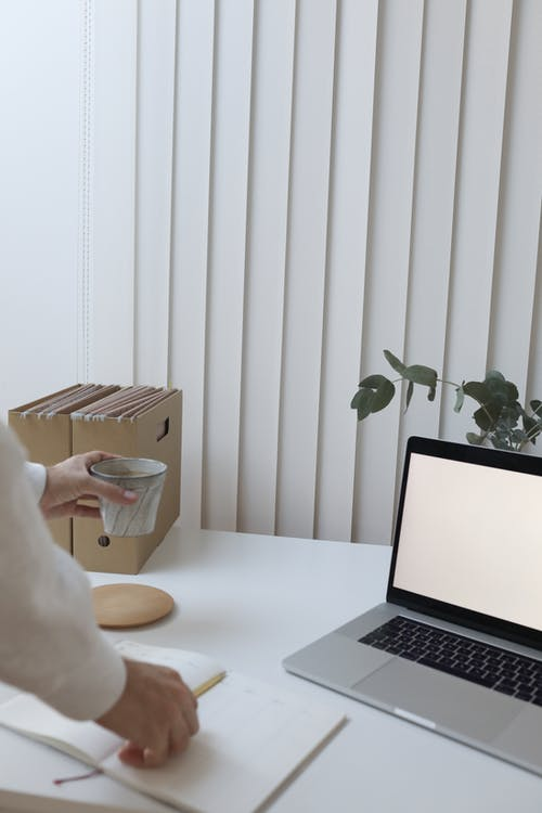 Crop faceless person standing near table with laptop and folders while drinking coffee
