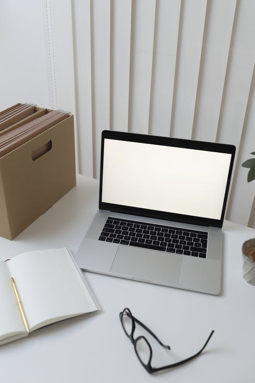 Laptop and papers on table in office