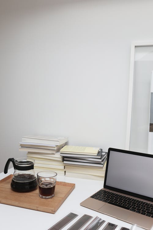 Laptop placed on desk near coffee glass and pile of books
