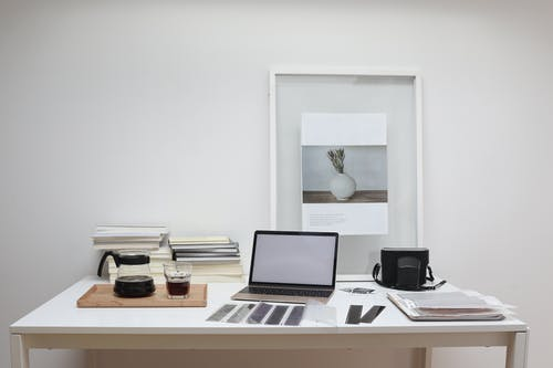 Modern laptop with blank screen arranged with retro filmstrips photo camera and framed picture placed on table near coffee and stack of books