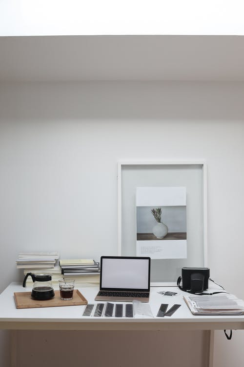 Photographer workplace with retro film camera and modern laptop