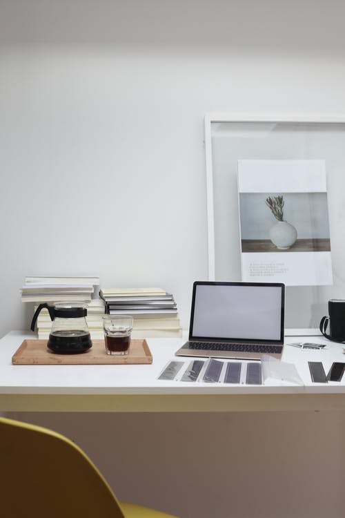 Working desk with laptop reversal film tapes and framed photo arranged with coffee glass and pot and books stack