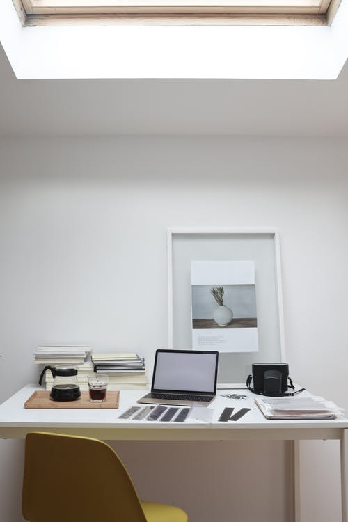 Netbook with white screen and retro camera placed on table with filmstrips and coffee glass during printing photos in office