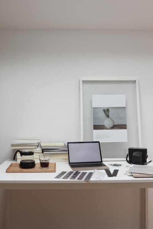 Photographer working desk with modern laptop and filmstrips scattered near film camera and glass of coffee decorated with framed picture
