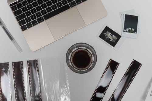 Top view of coffee cup with vintage instant photos and negative film strips placed on table with opened laptop