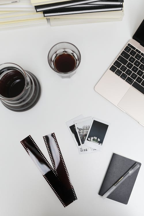 Laptop with photographic films and instant photos placed on desk near coffee glass