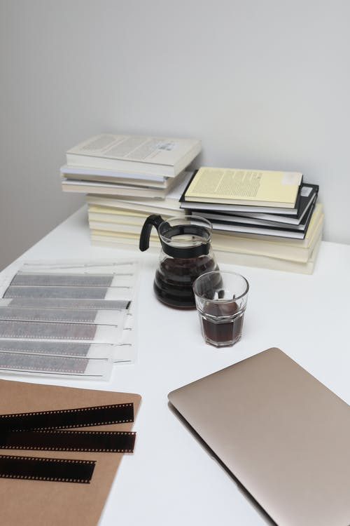 High angle of coffee glass and pot arranged on table with laptop near filmstrips and pile of books