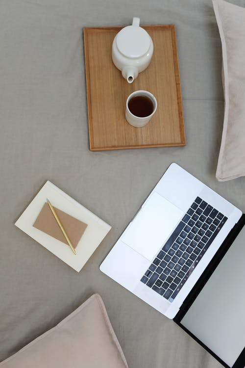 Top view of opened laptop with white screen and wooden tray with coffee set placed on comfortable bed with notebook and pen during distance lesson at home