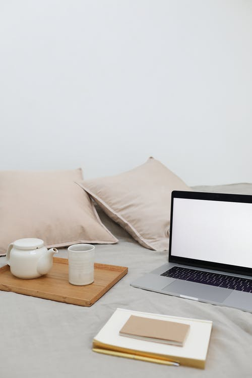 Jotter and laptop arranged on bed near tray with tea set