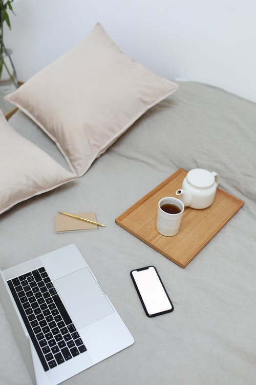Netbook and smartphone placed on bed near tray with tea set