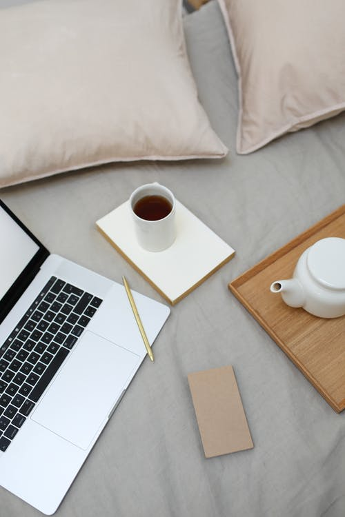 High angle of coffee cup and pot arranged on comfortable bed near opened laptop during remote work