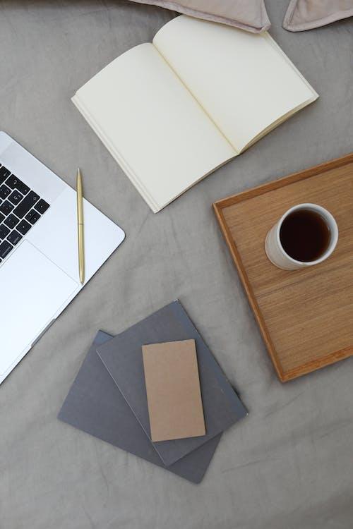 白いテーブルの上の茶色と灰色のタブレットコンピューター