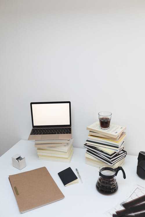 Opened laptop with empty screen placed on stack of books placed on white table against white wall in light room