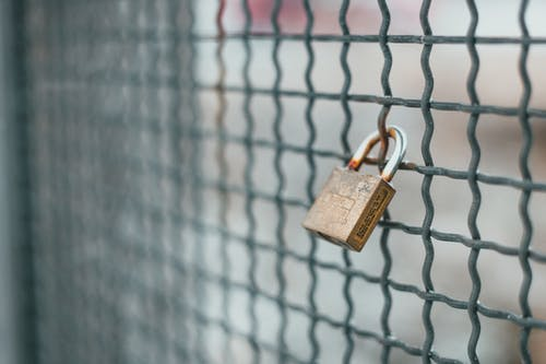 Small iron lock hanging on rusty metal grid for protection and safety of private area