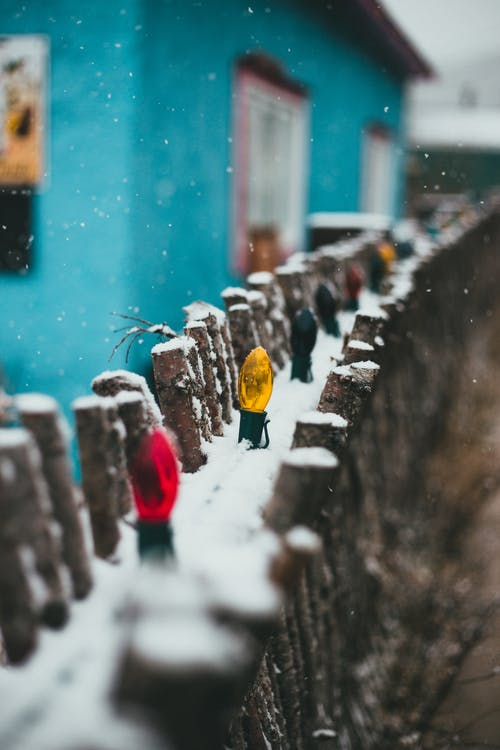 Bright multicolored garland hanging on wooden fence of rural house in village under snowfall