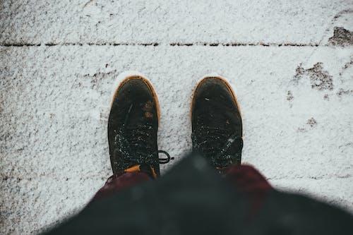 Person in sneakers standing on snowy wooden floor