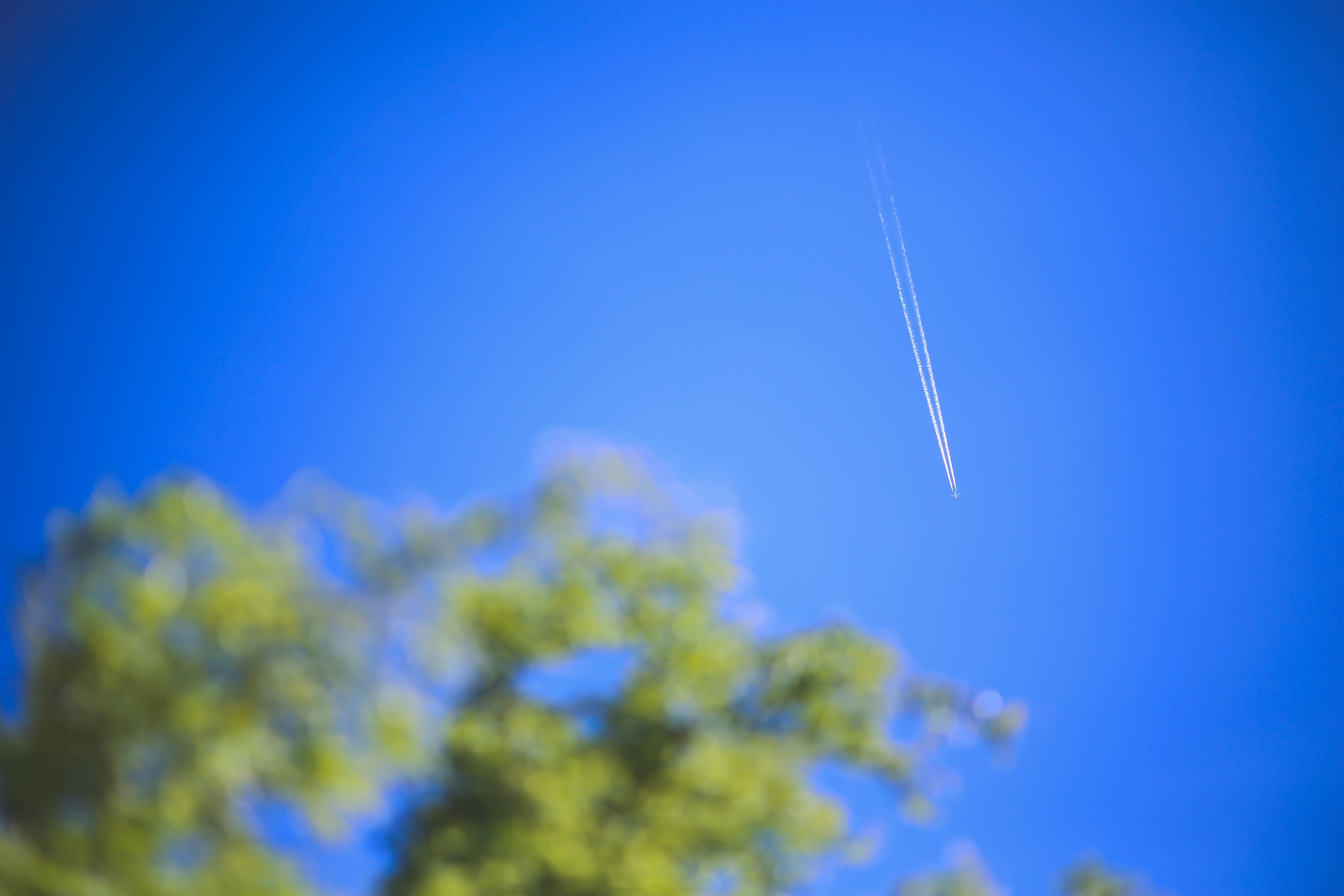 Passenger jet flying high in clear blue sky, leaving long white trail