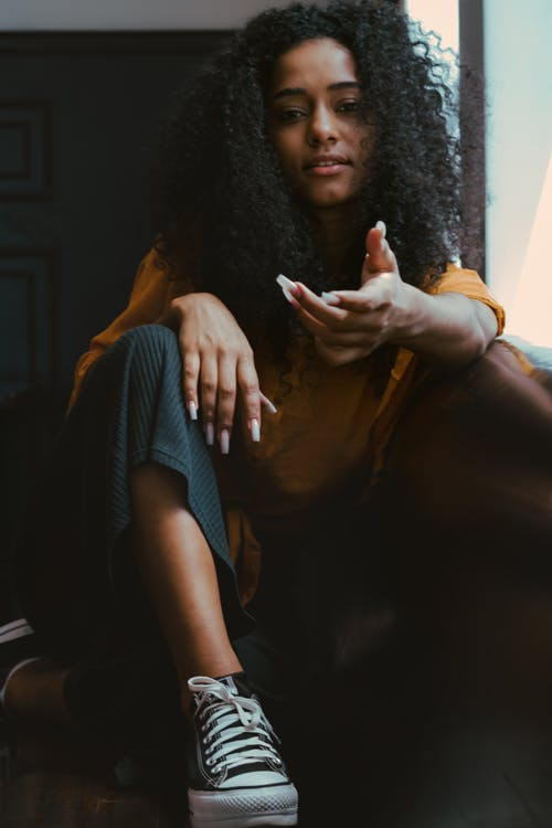 Young African American female with curly black hair sitting on floor with legs crossed and looking at camera