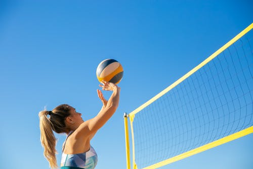 Woman in White Bikini Holding Yellow Volleyball Under Blue Sky