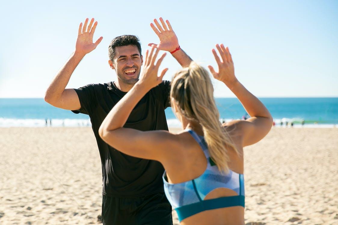 2 Women in Blue and Black Bikini Top on Beach