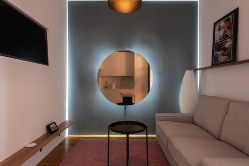 Modern living room with illuminated mirror on wall