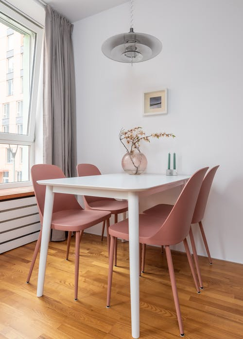 Modern interior of dining room with chairs and table decorated with tender branches of sakura