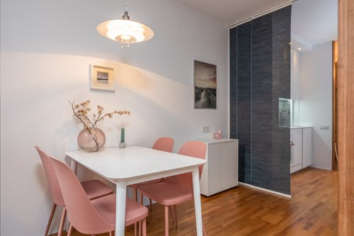 Stylish room with white table with glass vase near pink chairs and painting on wall with light lamp