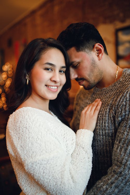 Loving ethnic couple in warm clothes embracing