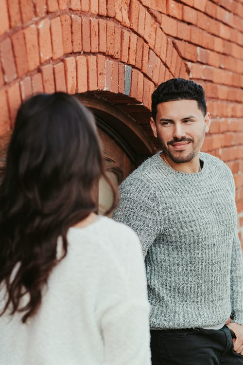 Young cheerful ethnic male with beard in sweater looking at anonymous girlfriend near brick wall
