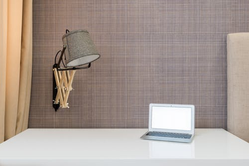 Interior of workplace with opened netbook on white table near wall with lamp