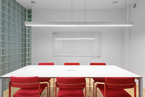 Interior of office with white table near red stools and whiteboard on wall near lamp and glass wall