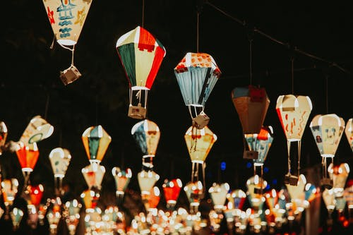 Abundance of traditional multicolored glowing lanterns painted in oriental style hanging on street in night time on blurred background during